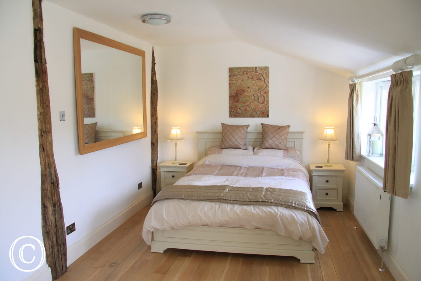 Double bed, cream linen and exposed woodwork.