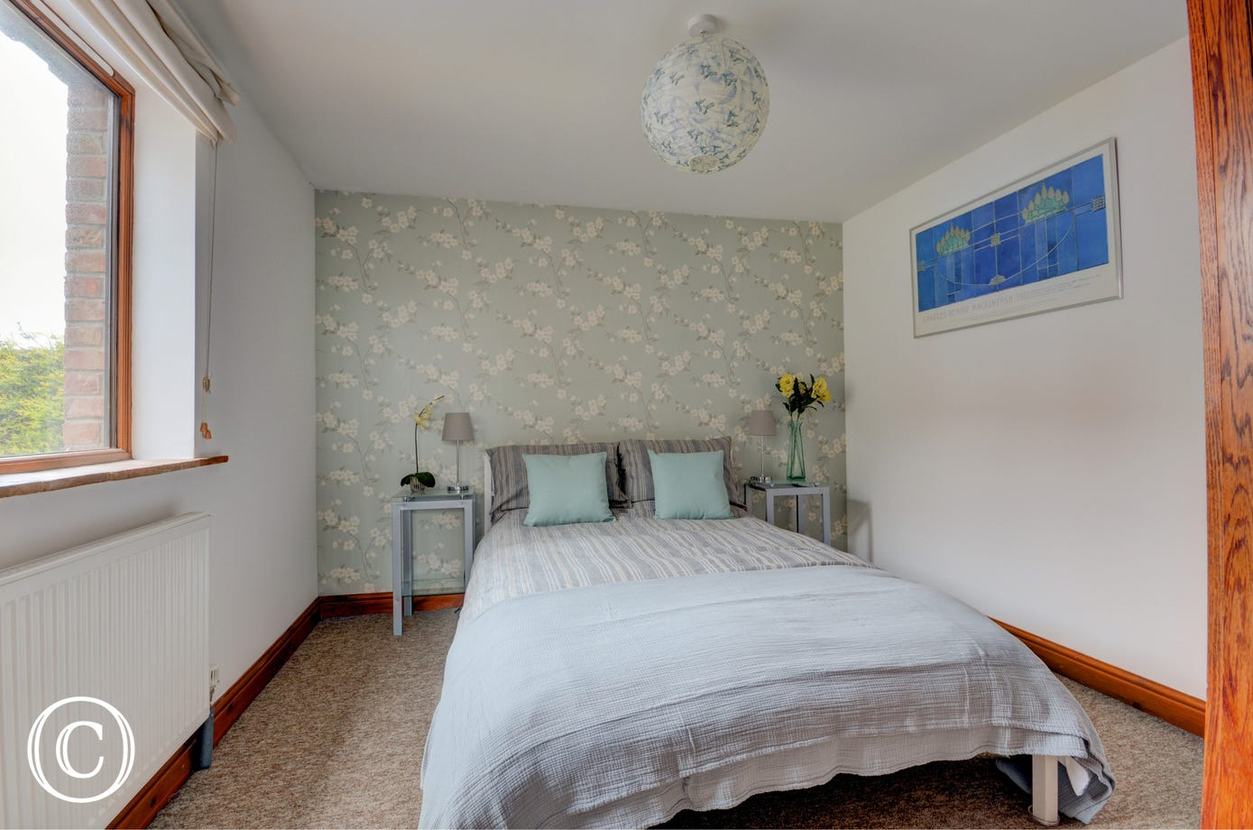 Contemporary furniture and furnishings in this bright double bedded second bedroom.