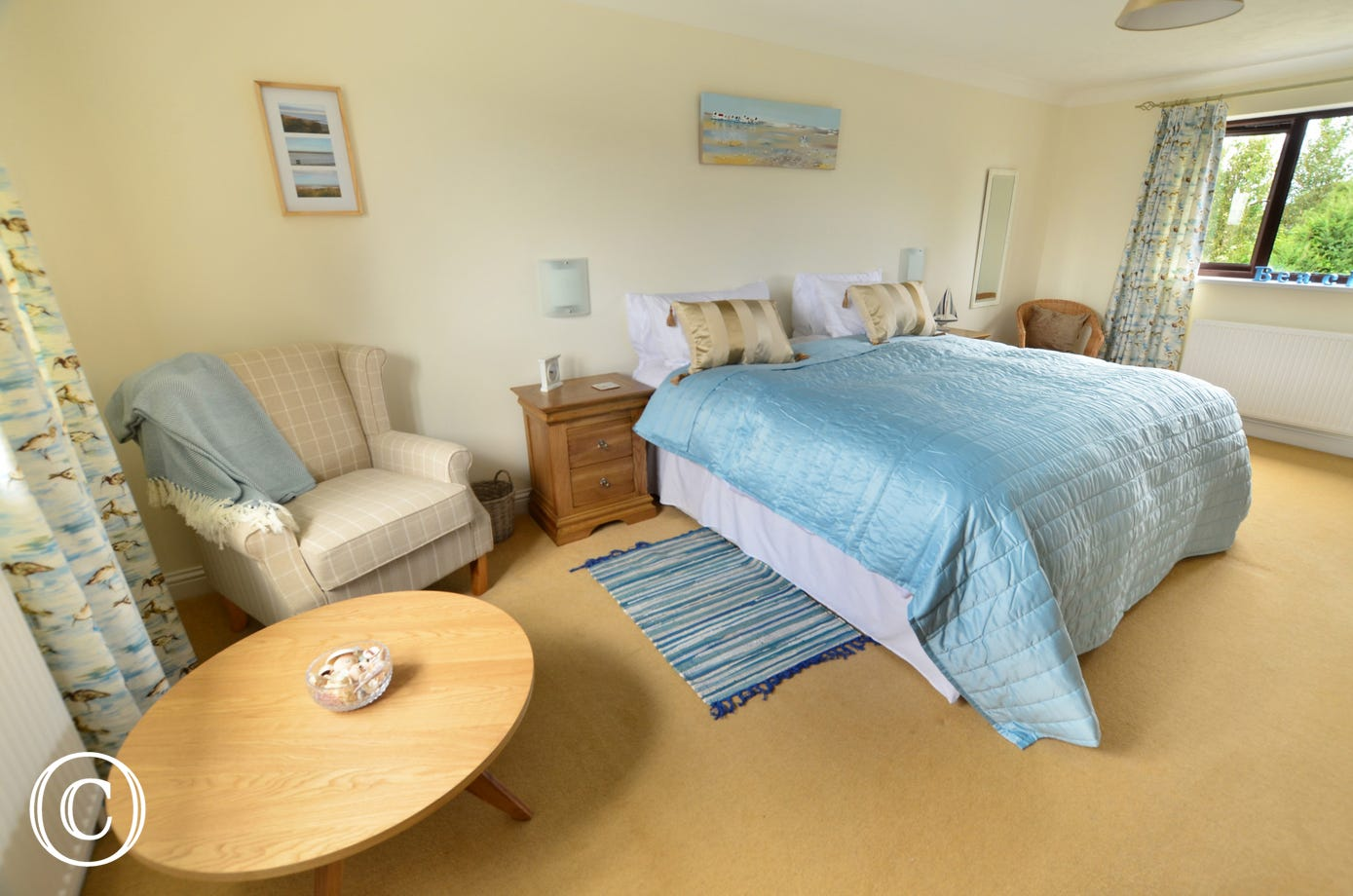 Double aspect bedroom with comfortable chairs and a table