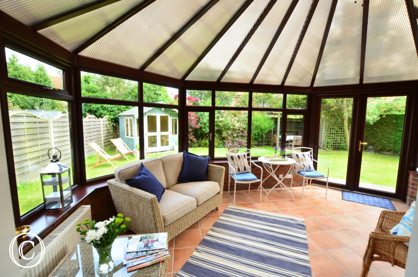 Large tiled conservatory with comfortable seating and lovely views of the garden
