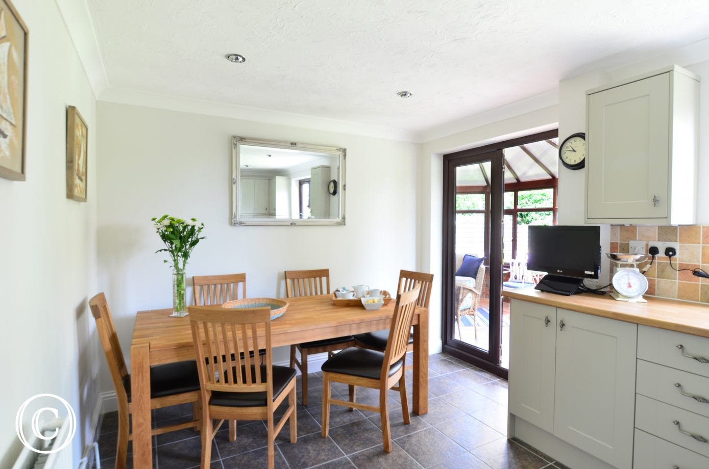 Lovely dining area with table and chairs and door leading to the conservatory