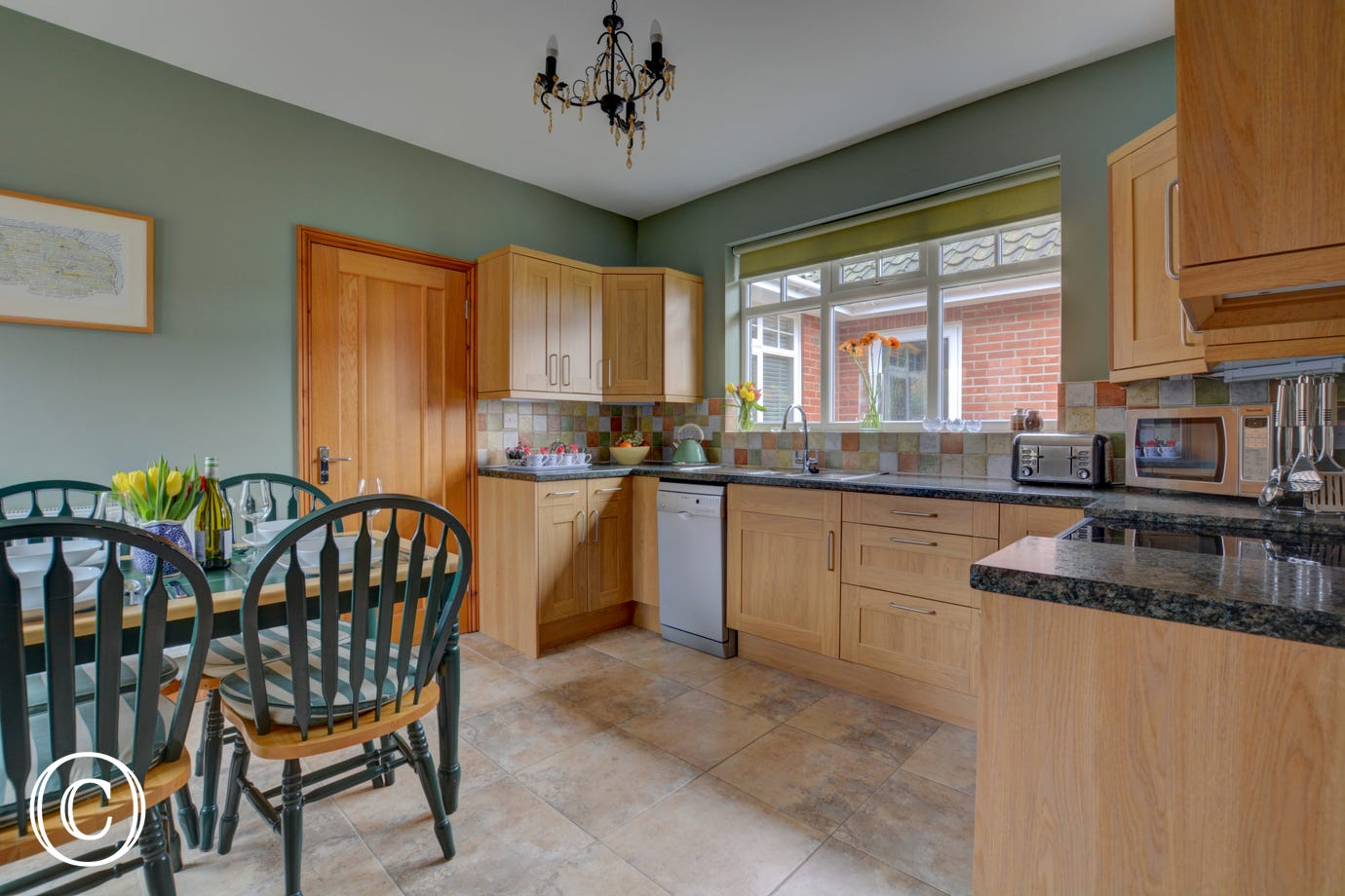 Kitchen with table and chairs, electric oven and induction hob.