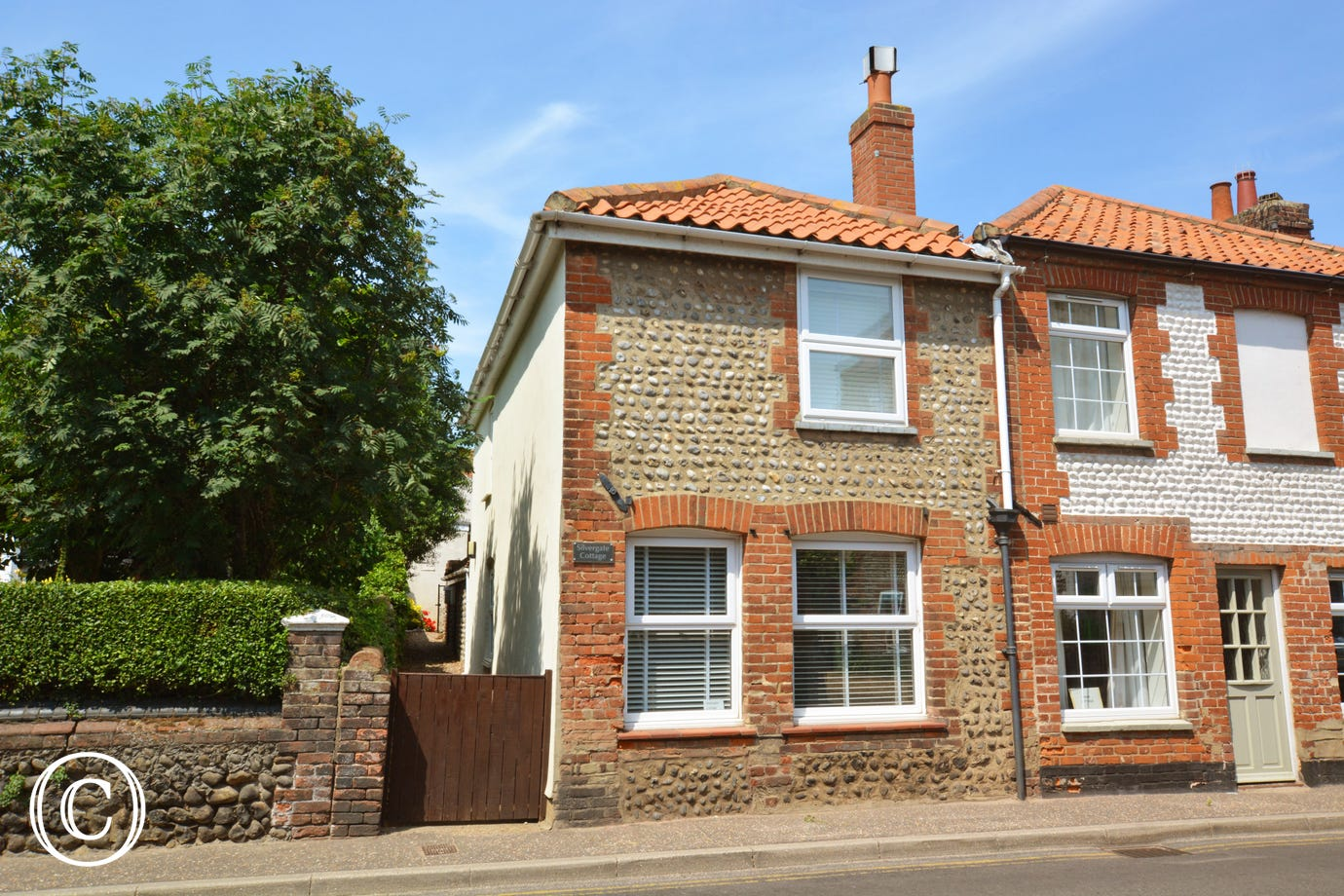 Exterior image of this charming brick and flint cottage