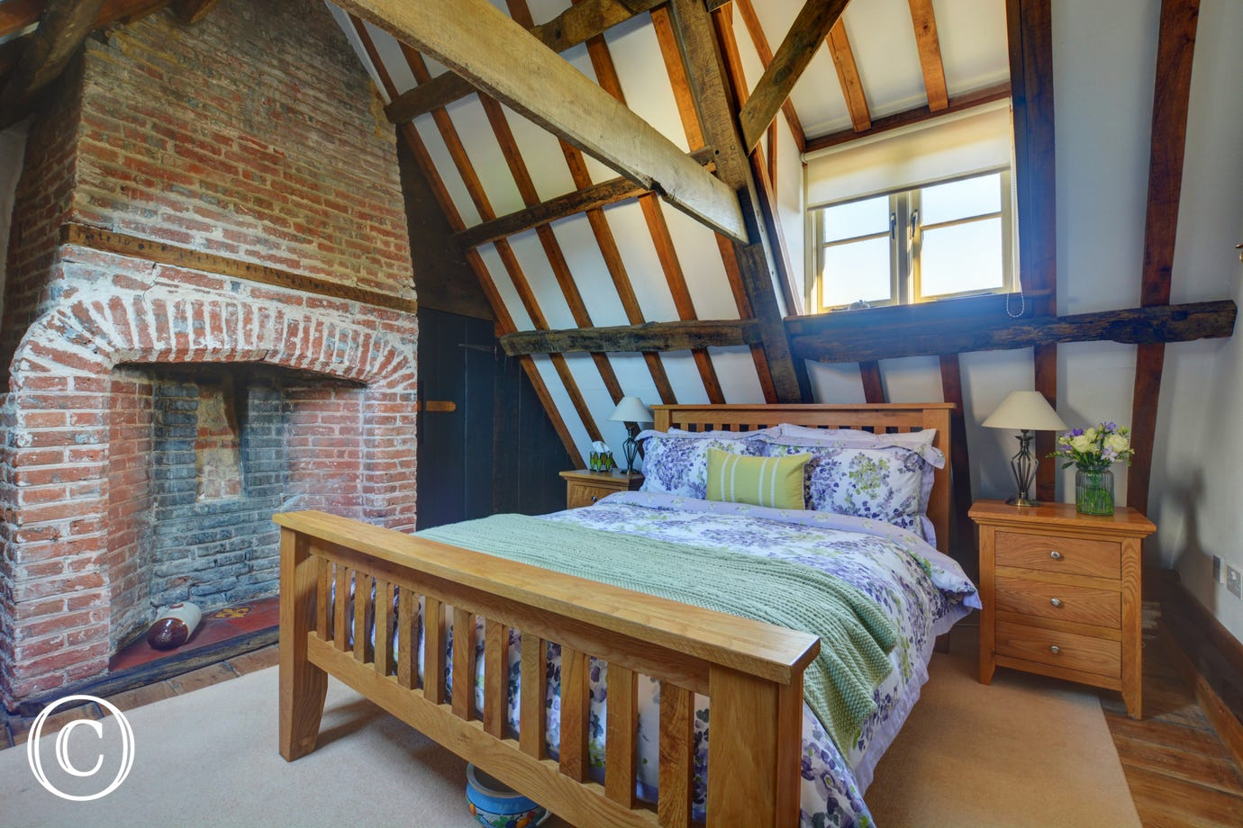 Beautiful double bedroom with a double bed and an exposed brick feature fireplace