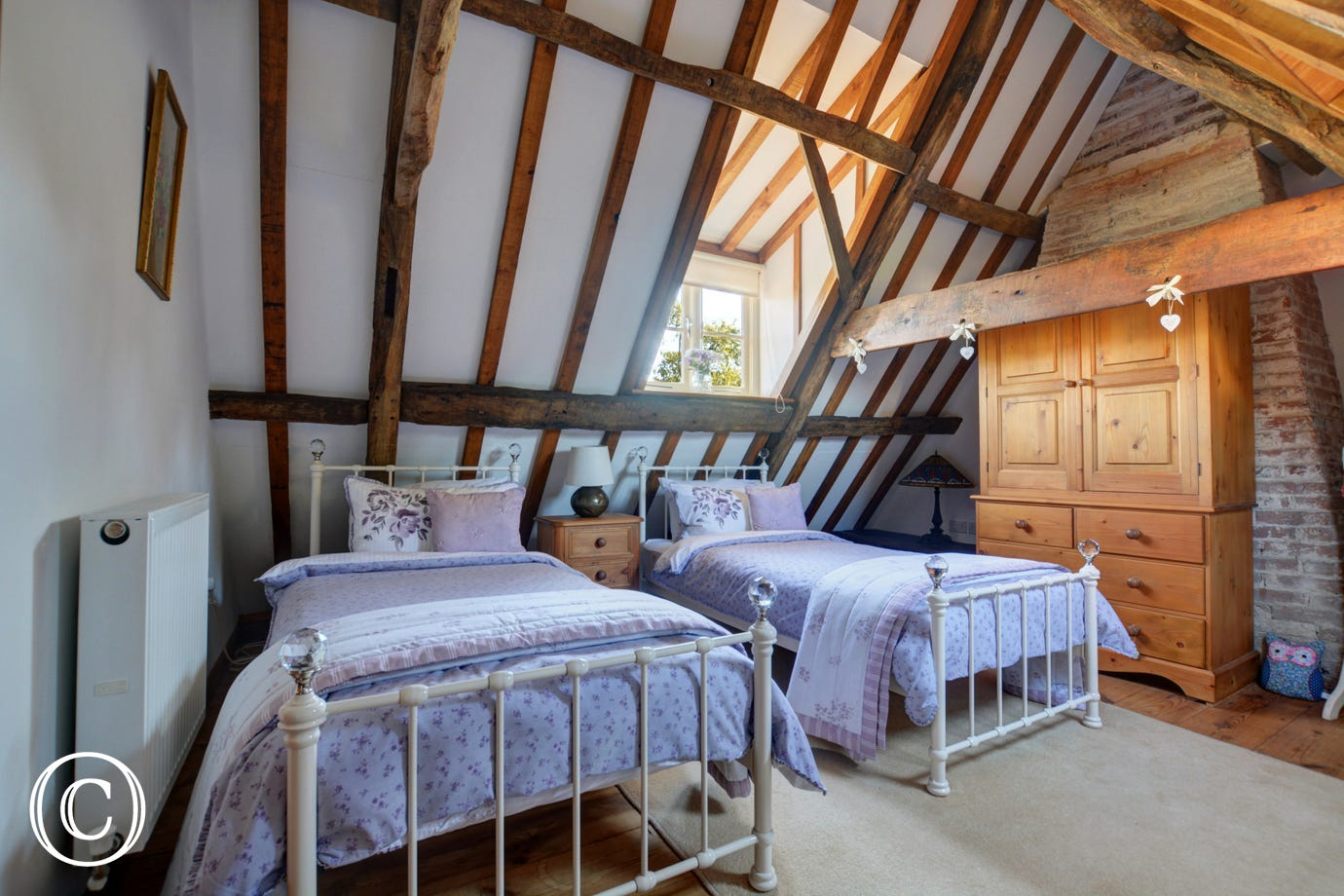 Super double bedroom with twin beds, exposed brickwork and character beams