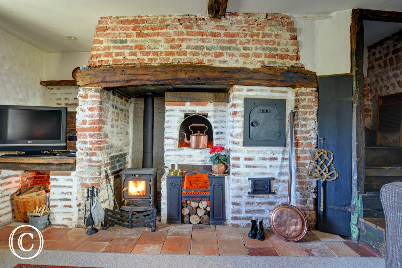 View of large inglenook fireplace with pot-bellied stove and ornamental baker's oven
