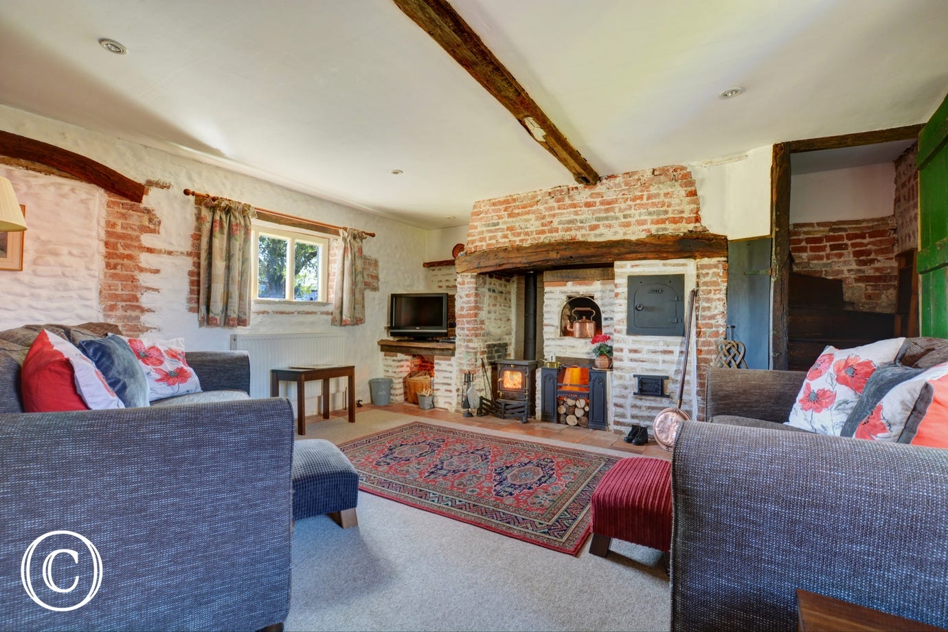 Sitting room with lots of character, inglenook fireplace with pot-bellied stove and an original ornamental baker's oven