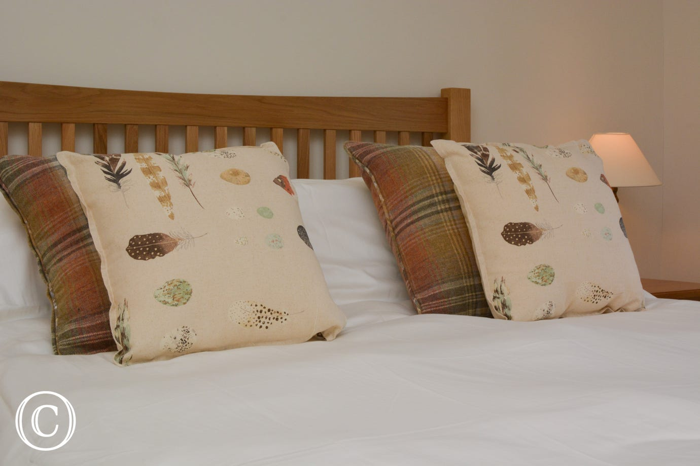 Bed made up with white linen and tasteful cushions