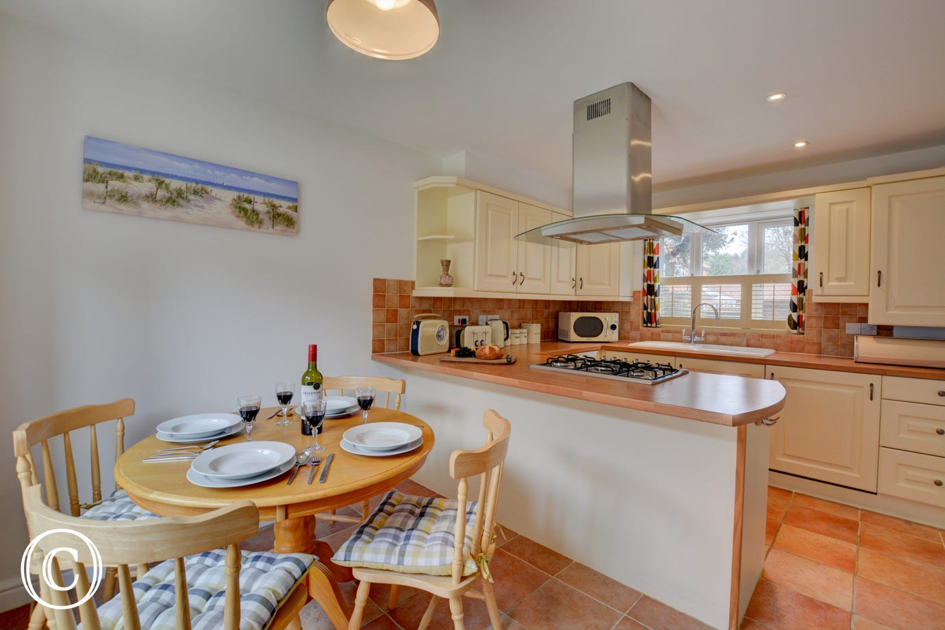 Modern kitchen & dining room area with gas hob, extractor & dining table with four chairs