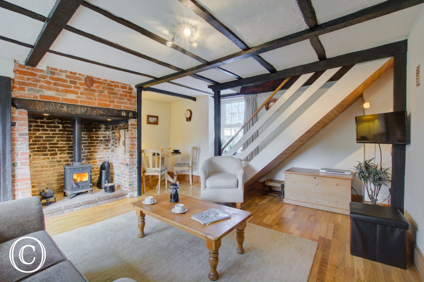 Sitting room with open beams and inglenook fireplace