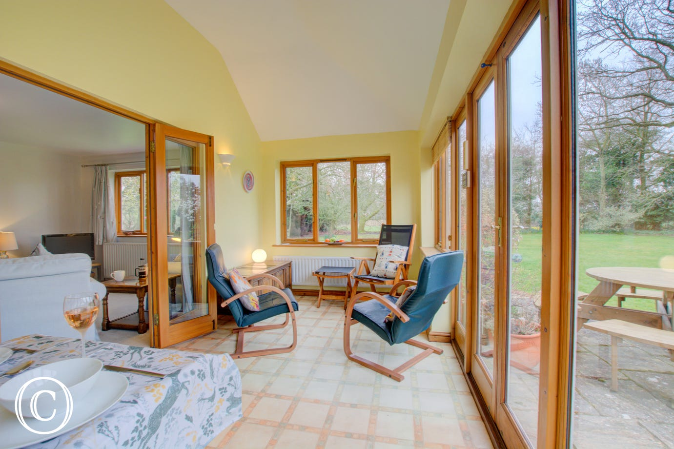 A bright sun room has French doors onto the sunny patio area.
