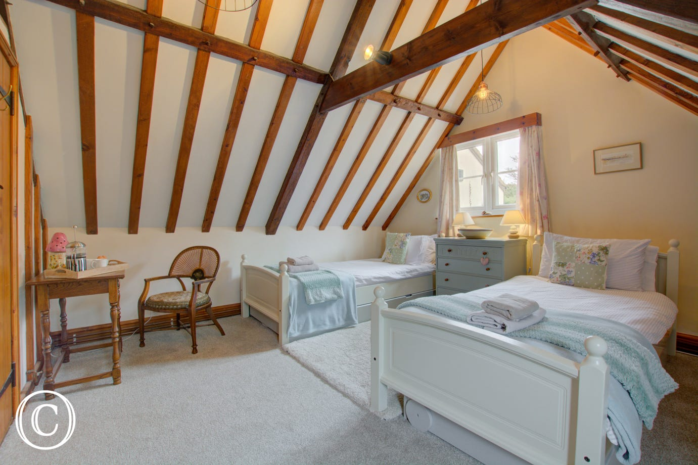 Bedroom two is another delightful room with rustic beams and has two single beds