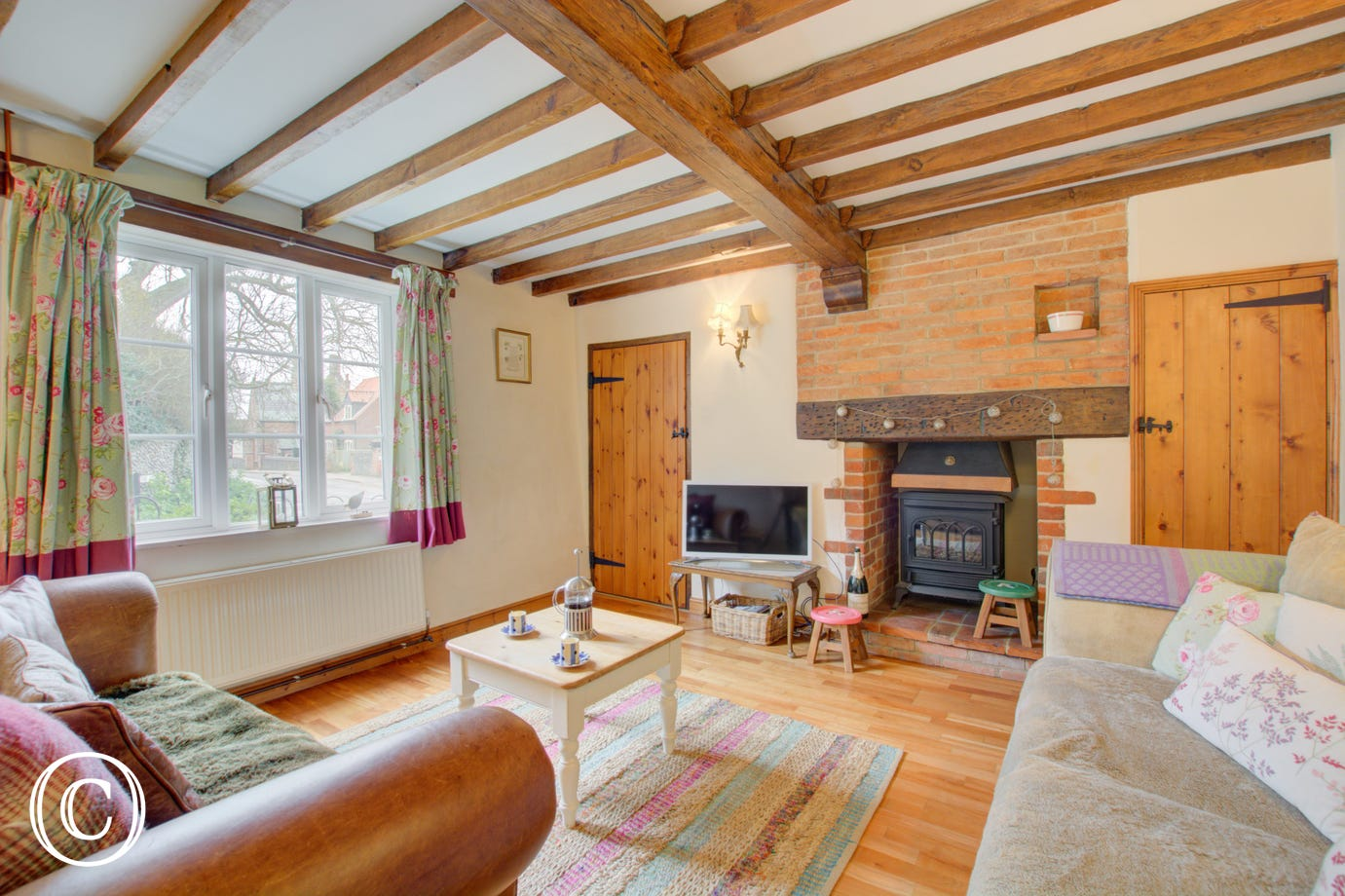 The sitting room is a lovely cosy space with rustic open beams and an electric woodburner
