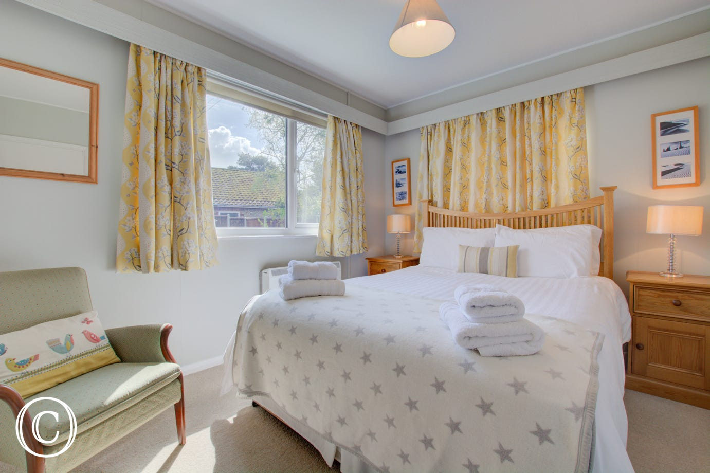 A light & airy room with a king-size bed, bedside cabinets & lighting