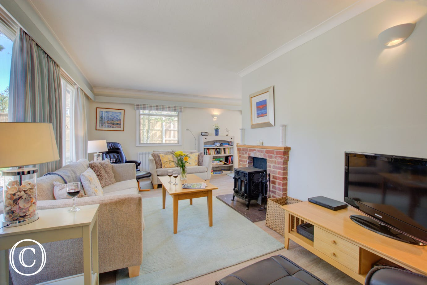 An attractive well-furnished room which has large picture windows, comfortable seating and a woodburner.