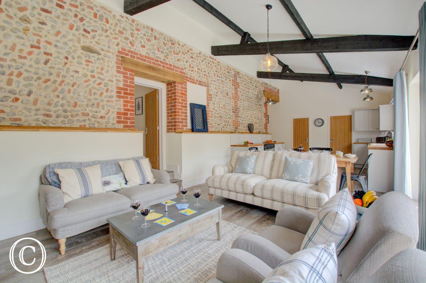Open plan living room with comfortable seating, exposed brickwork & beams.