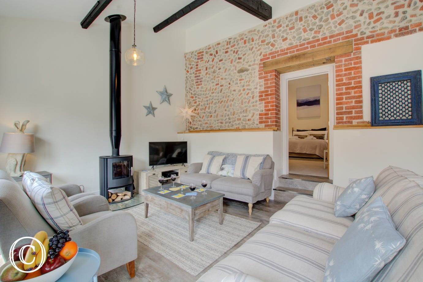 Open plan living room with comfortable seating, woodburner, tv & exposed brickwork
