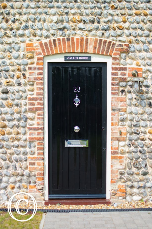 Gallus House front door surrounded by brick & flint