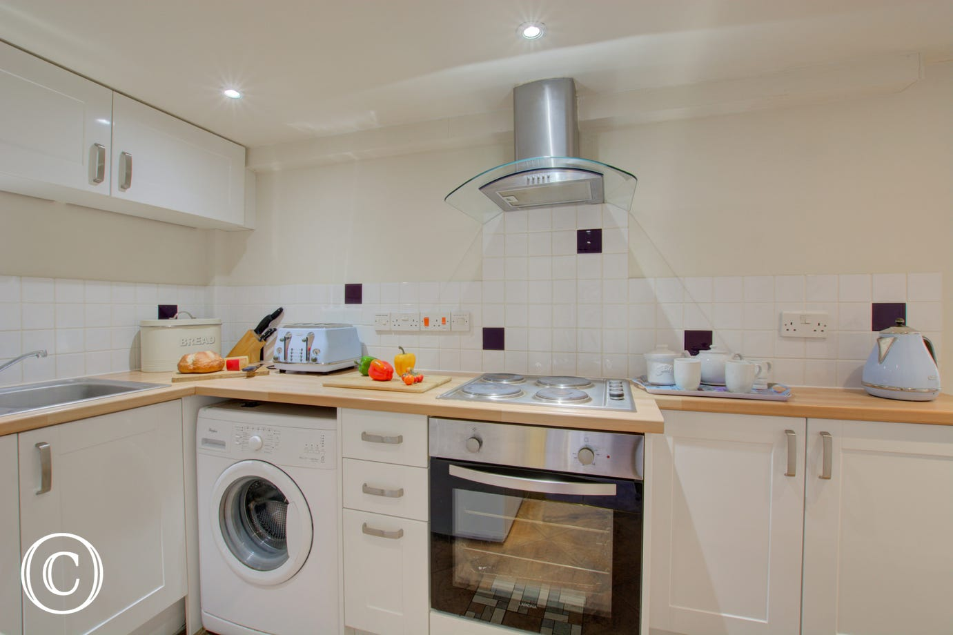 Modern fitted kitchen with  built-in electric oven, electric hob, fridge with icebox, microwave and washing machine