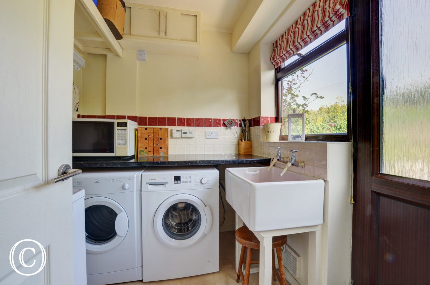 Utility room with washing machine, tumble dryer and sink