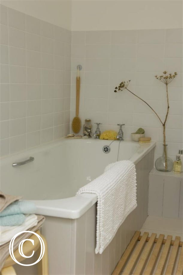 Tiled bathroom with a bath