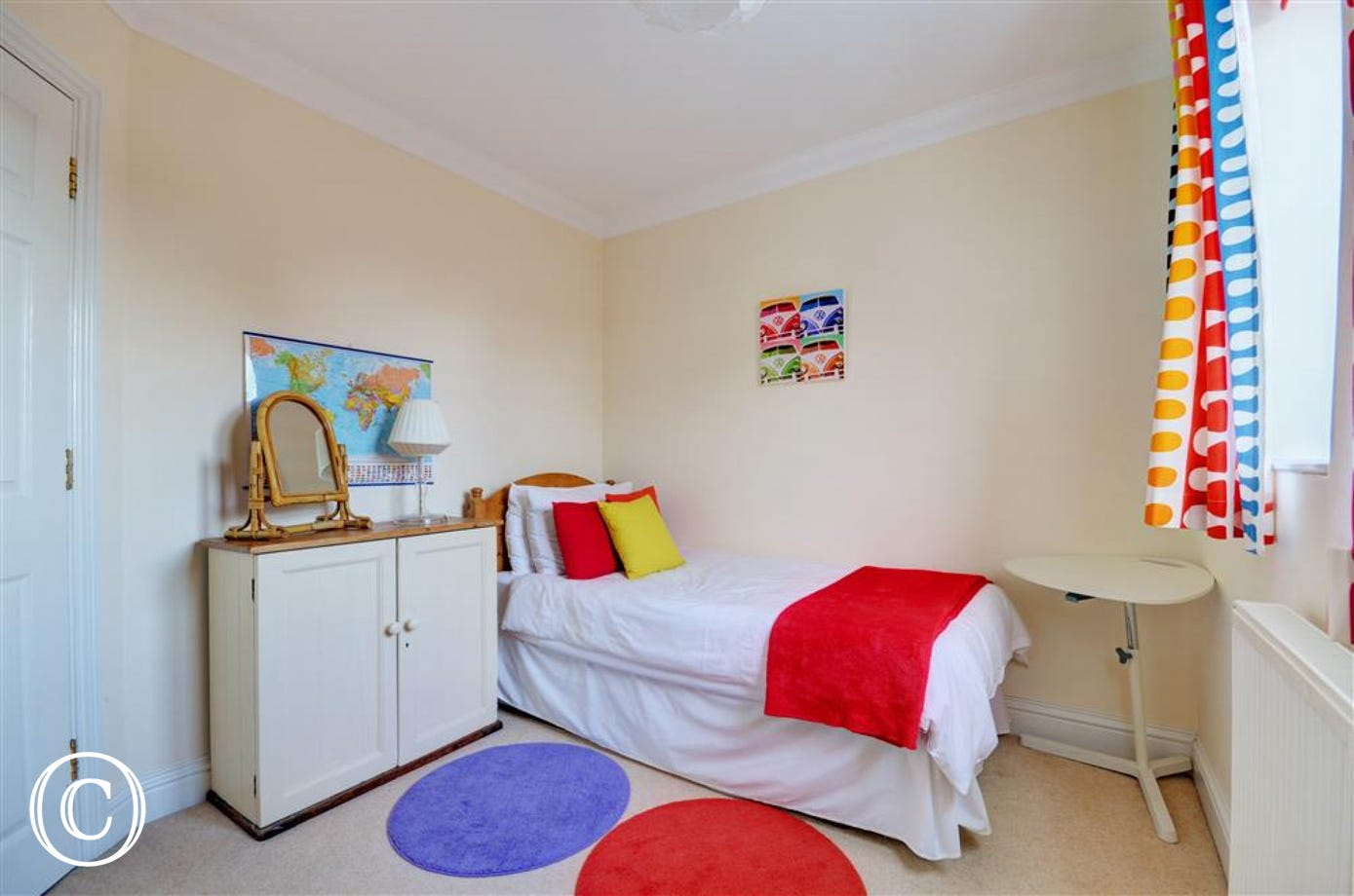 View of the single bedroom, with cupboards and cheery bright cushions and curtains.