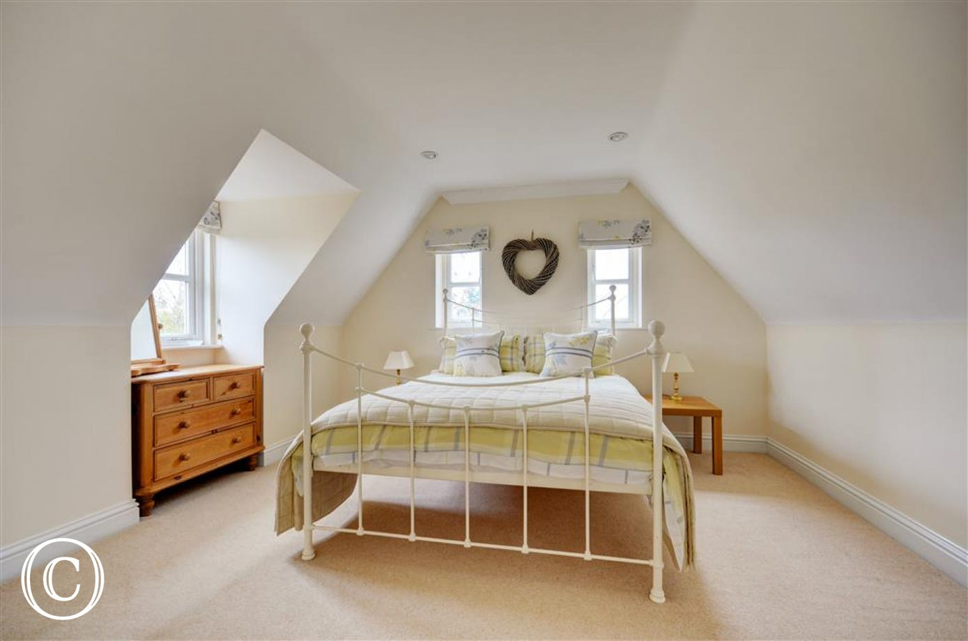 Lovely bedroom with Kingsize iron bed, sloped ceilings with chest of drawers in window recess.