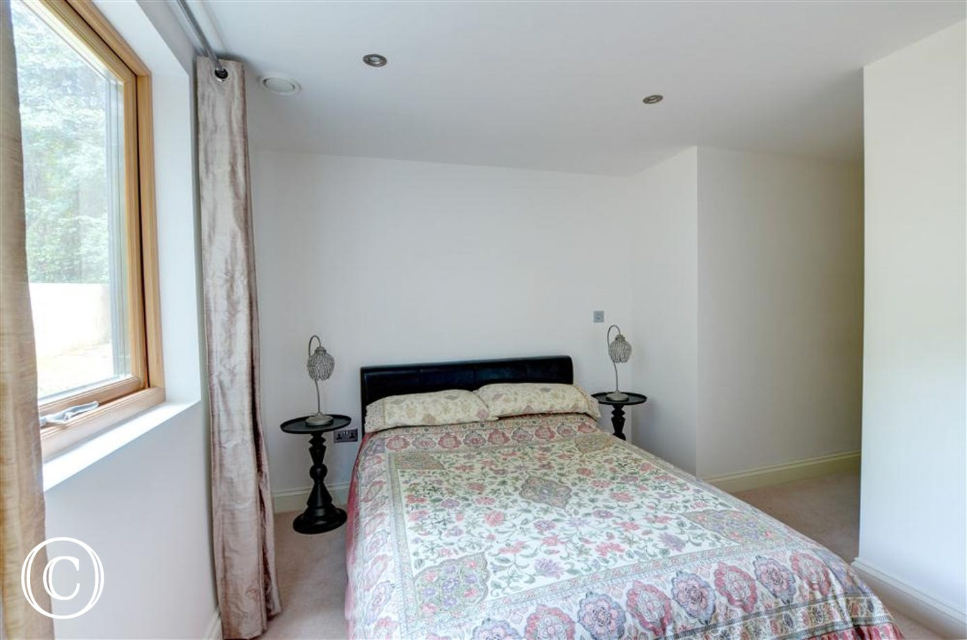This bedroom has a double bed and ornate bedside tables