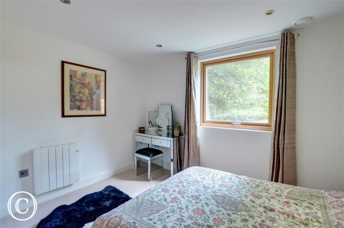 The master bedroom has an en-suite shower room, this view shows the dressing table and chair