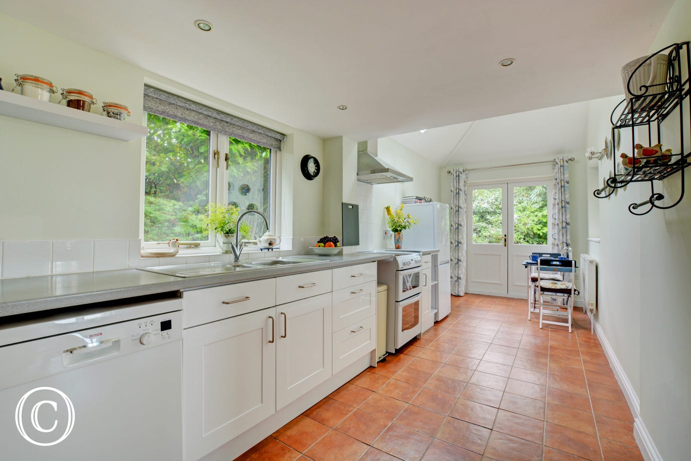 Light and airy kitchen with  built-in electric oven and hob, fridge/freezer, dishwasher, microwave and bistro table and chairs for two