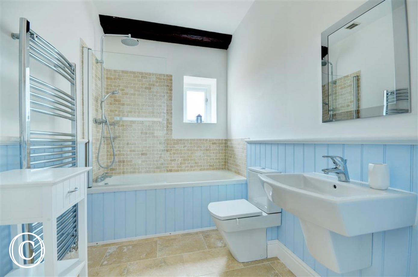 Lovely bright bathroom with bath and over bath rain shower