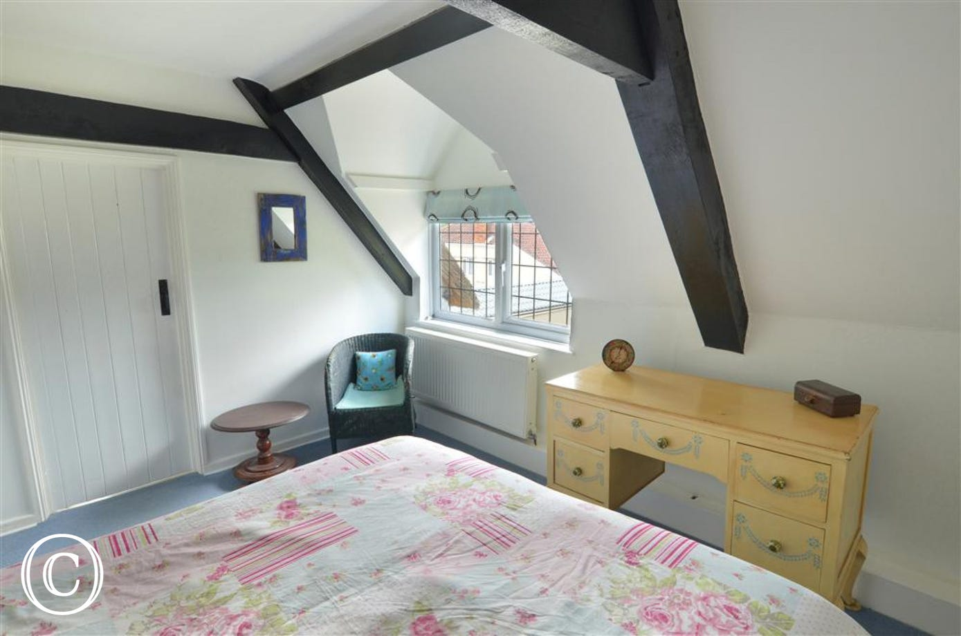 View of bedroom1, showing sloped ceiling with beams and dormer window, with dressing table below.