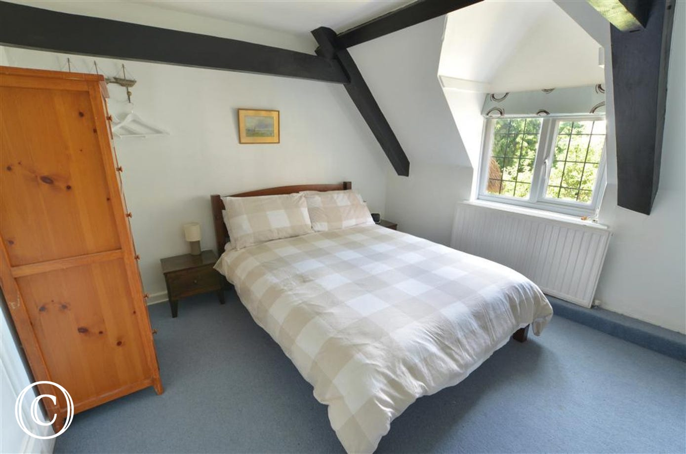 View of bedroom 2 showing double bed, beams, dormer window dressed with a blind, with radiator below.