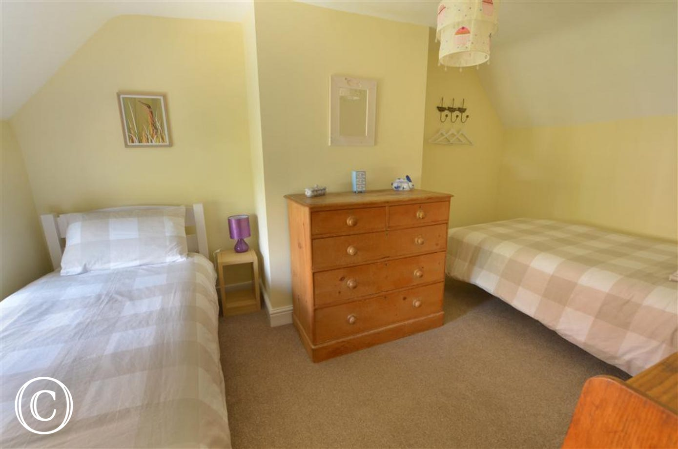 View of twin bedded room, bed positioned either side of room with pine chest of drawers in front of chimney breast, room painted in cream with fresh bedlinen in a beige and white large check design.
