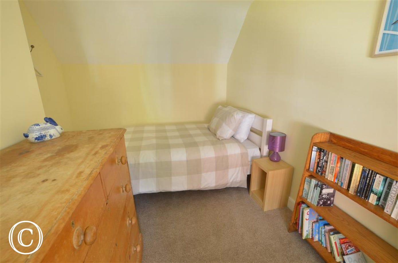View of bedroom 3 with single bed, book shelf and chest of drawers.