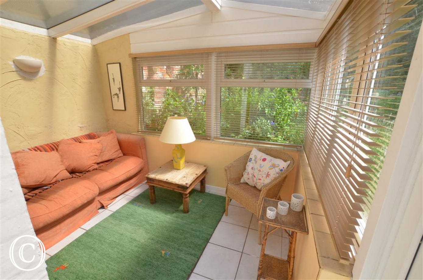 View of conservatory, venetian blinds at all windows, sofa, wicker chair and side tables.