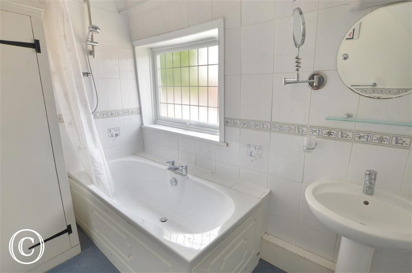 View of ensuite bathroom, with over bath shower and sink with mirror over.