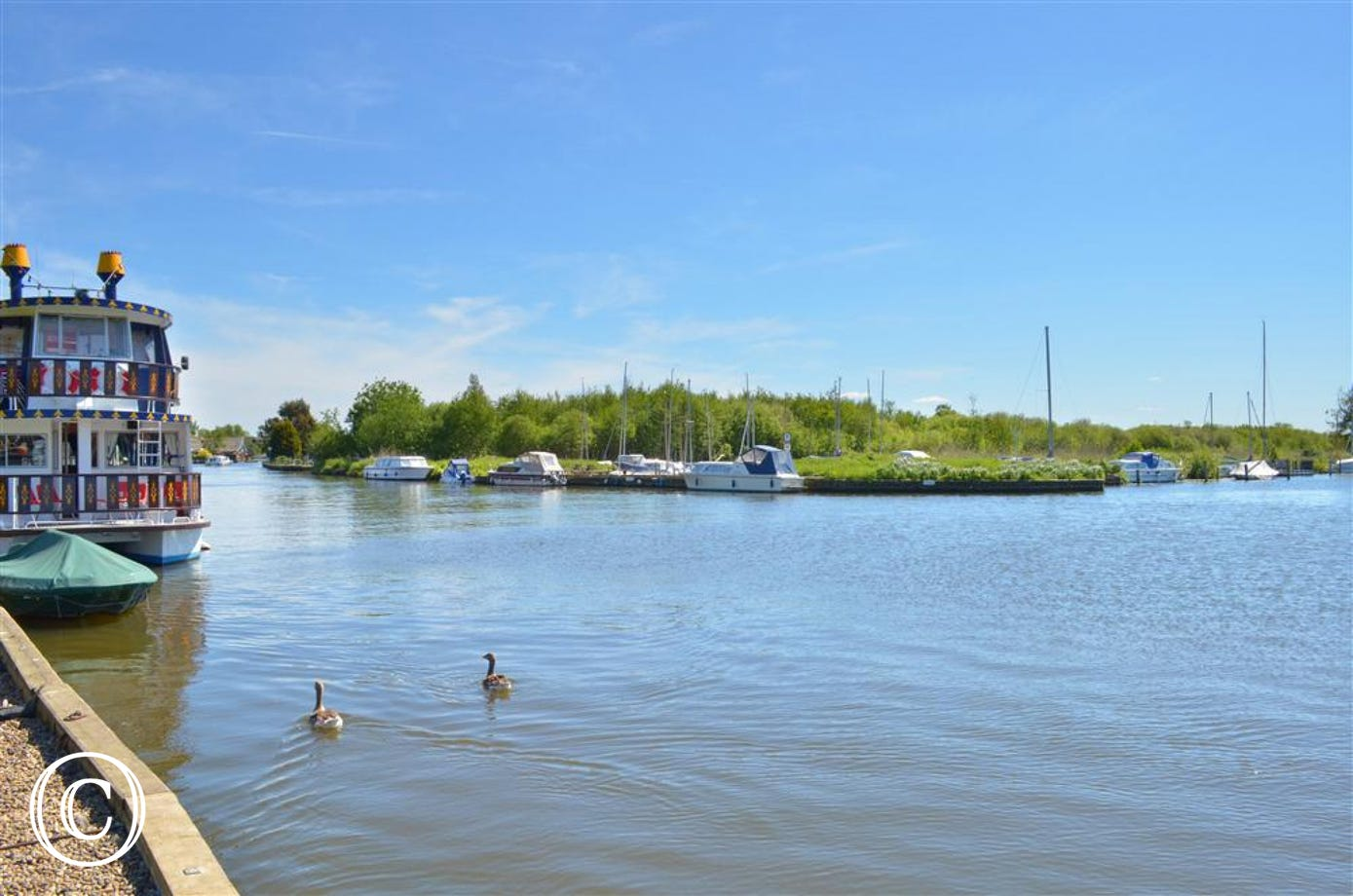 View of Horning Broad, with the boats moored to the side.