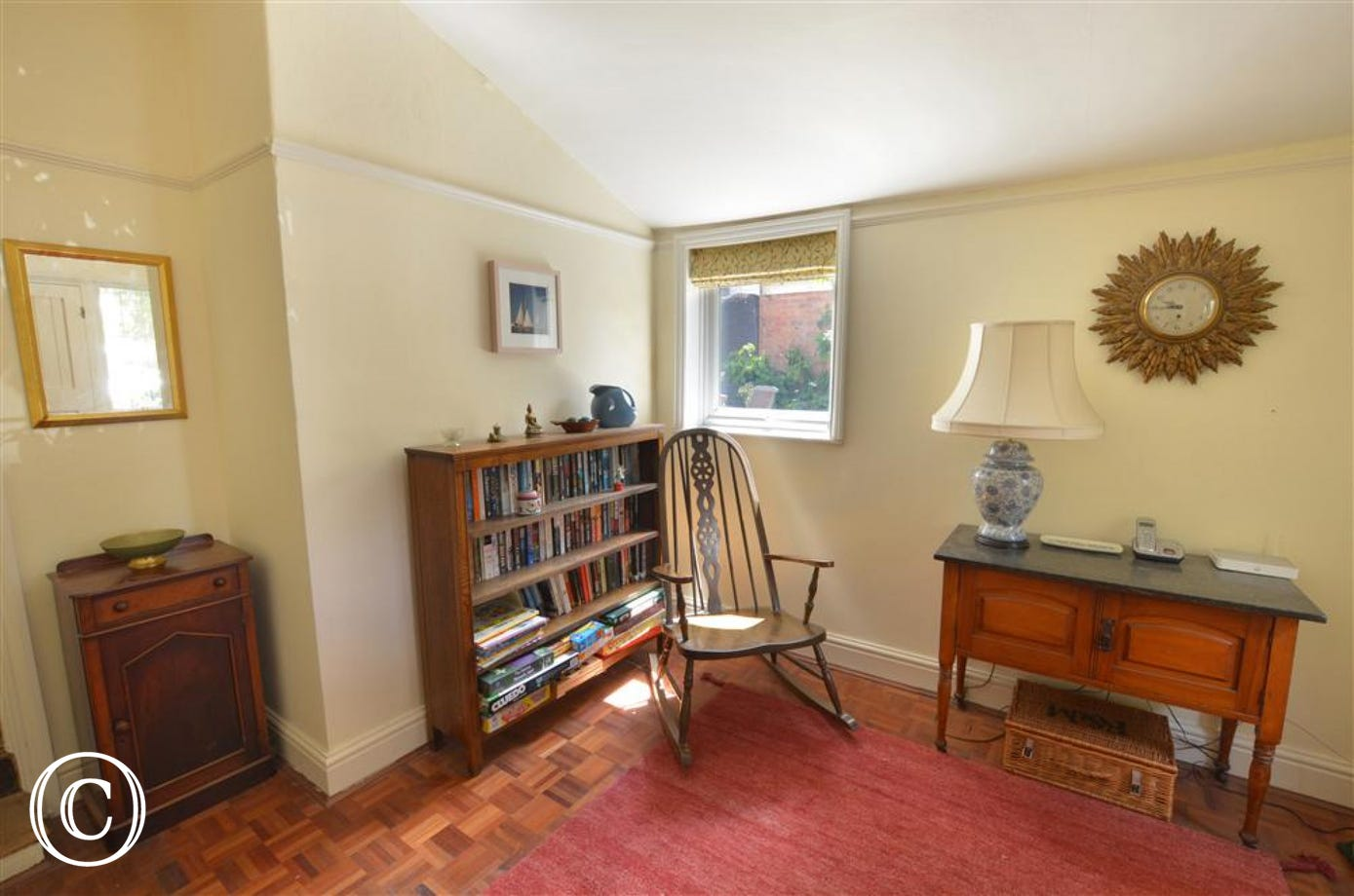 View of entrance Hall, with rocking chair, book shelf, side tables and lamp.