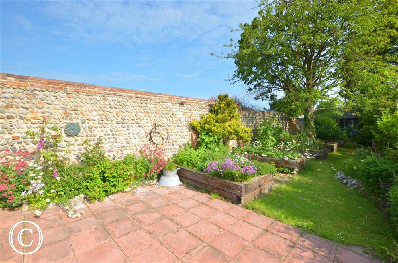 Fully enclosed garden with lawned area, raised herb beds, patio, garden furniture and barbecue, ideal for al fresco dining