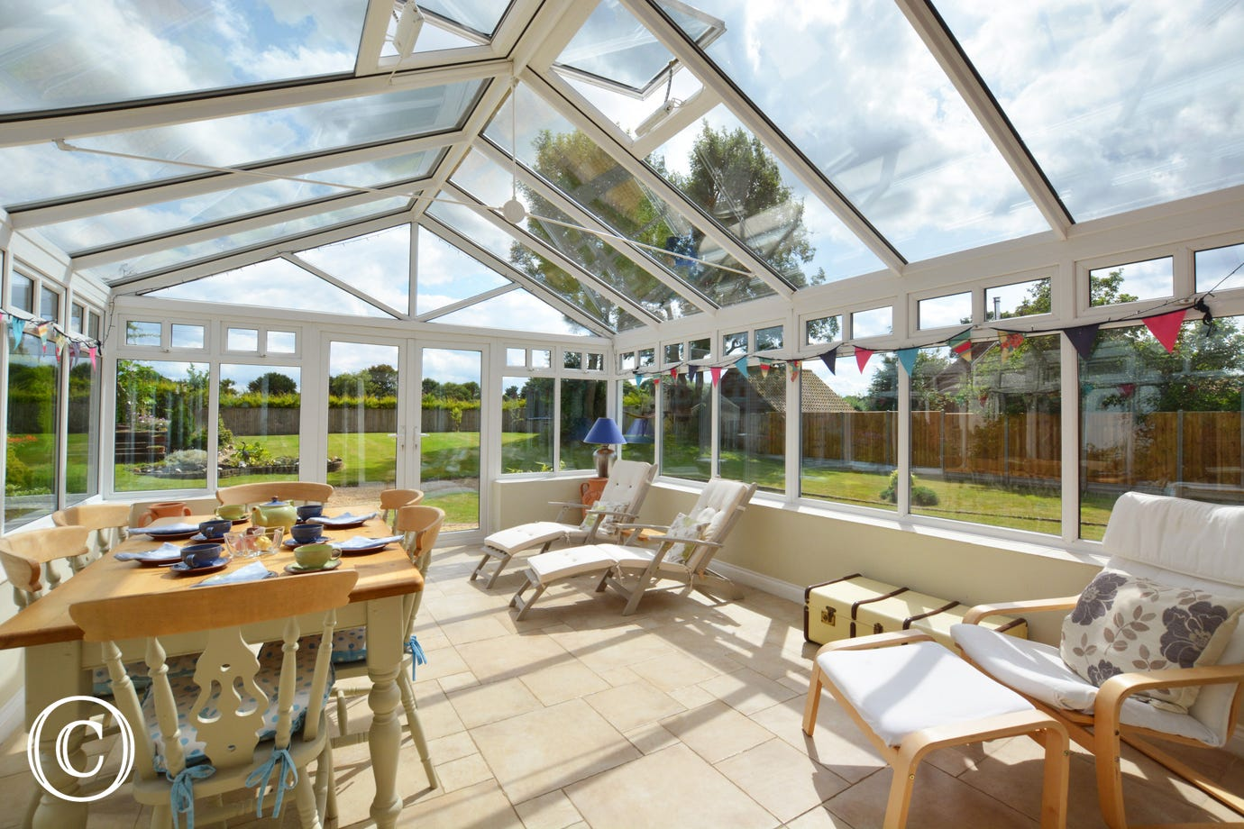 Conservatory with comfortable seating, and dining table with chairs