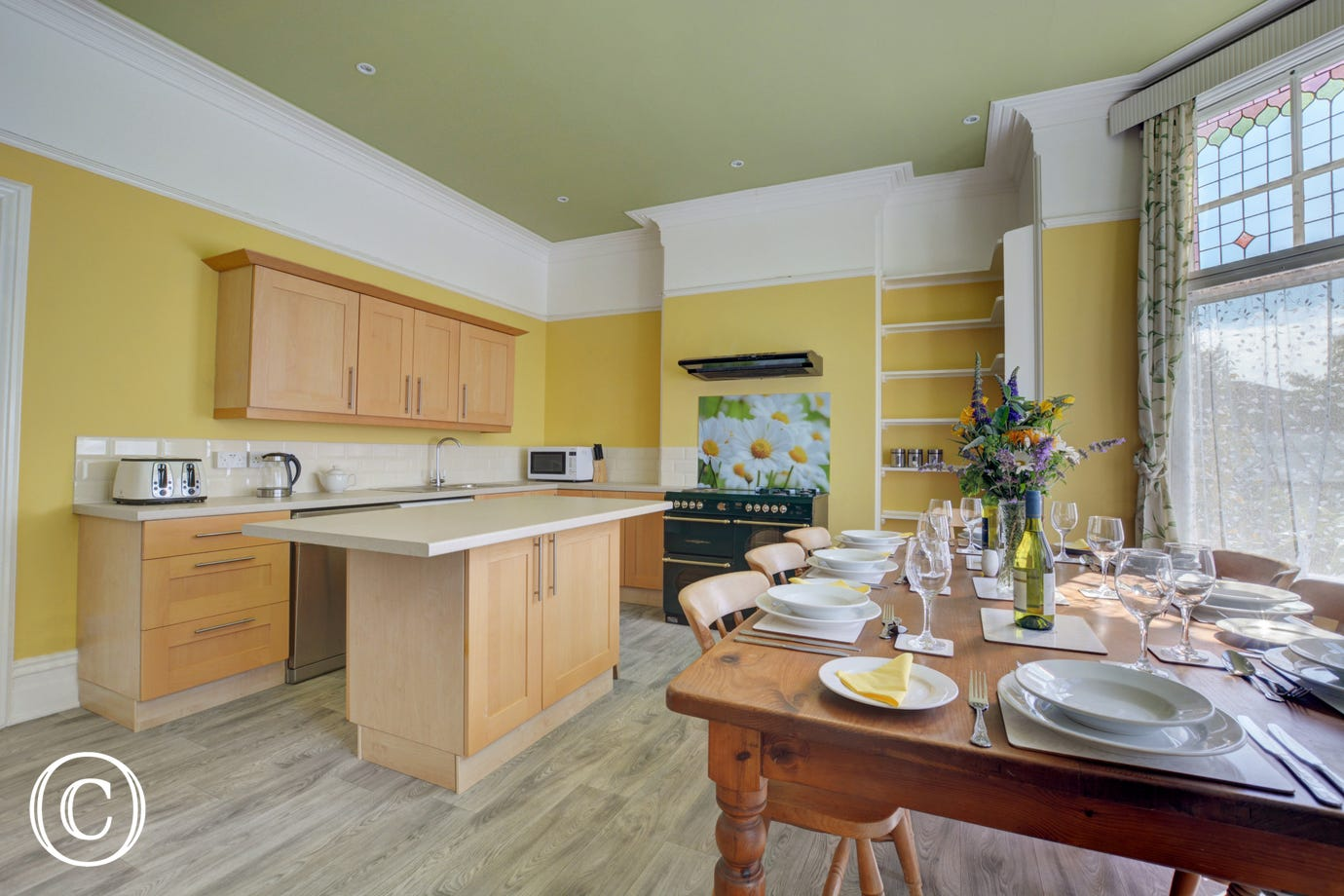 Kitchen with range cooker with two electric rings and three gas burners, electric oven and warming drawer, combination microwave, fridge/freezer, dishwasher, large dining table and eight chairs