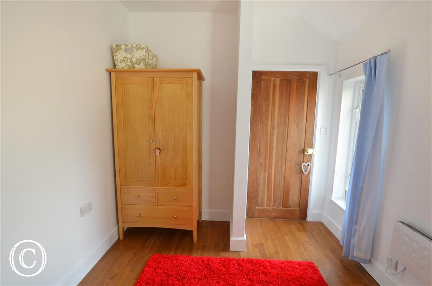 Twin bedroom with wardrobe and door out.