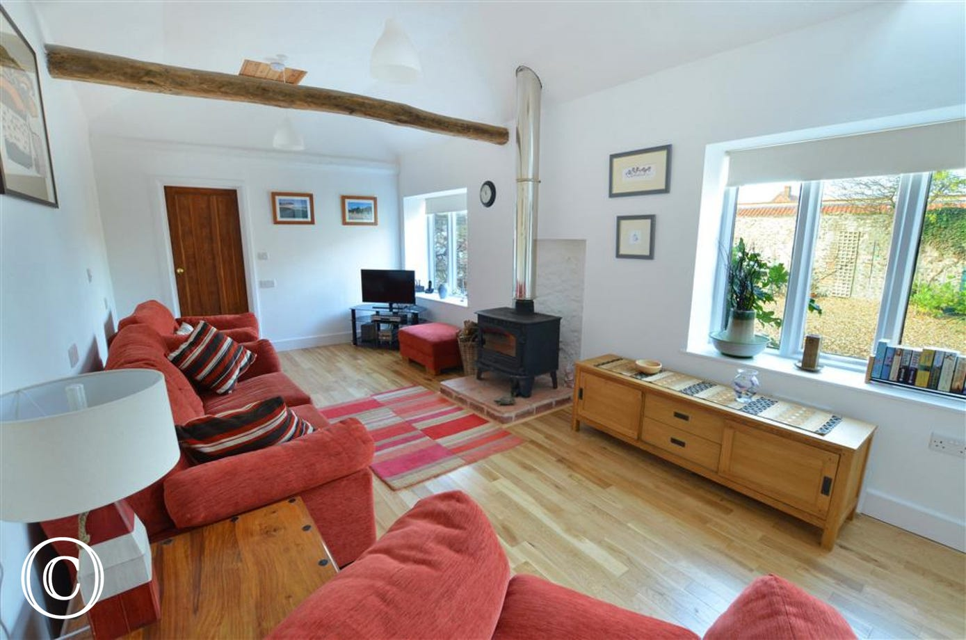View of family sized sitting room with TV, woodburner and low storage unit.