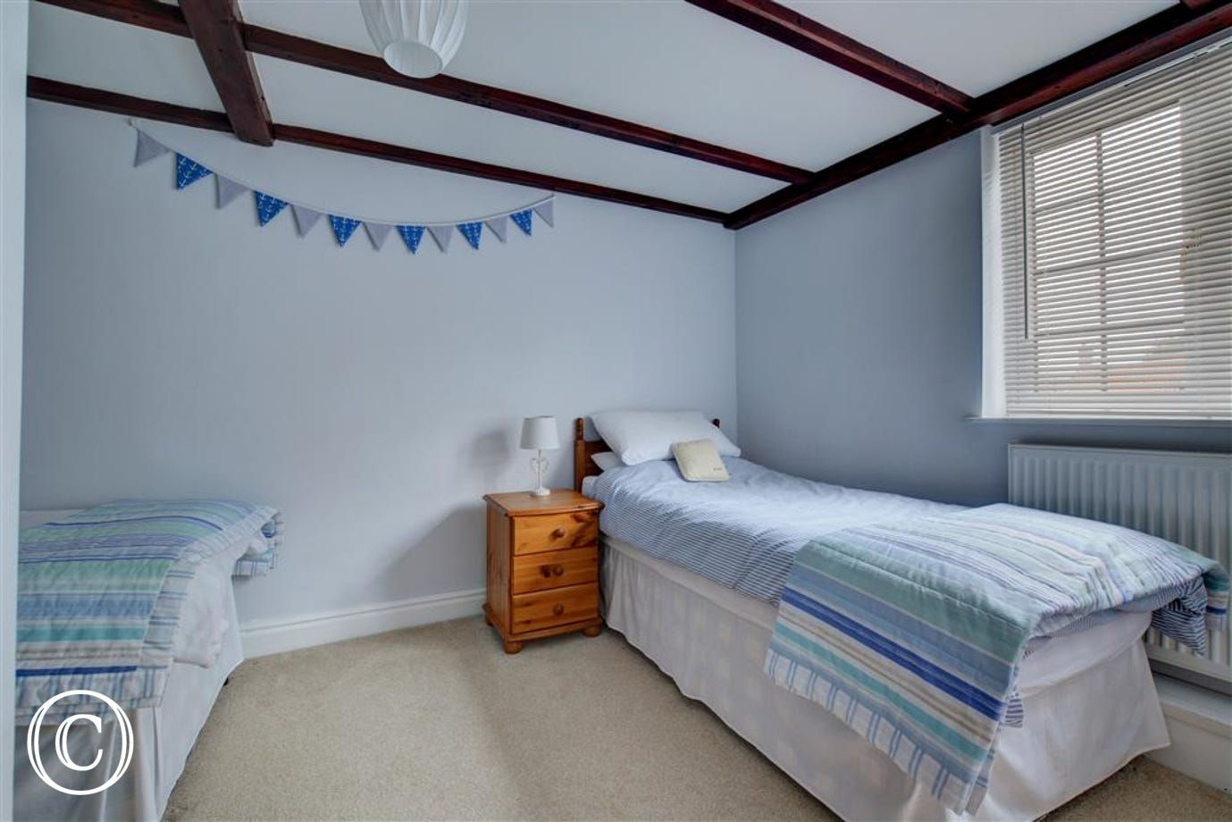 Bedroom three is a nautical themed room with twin beds