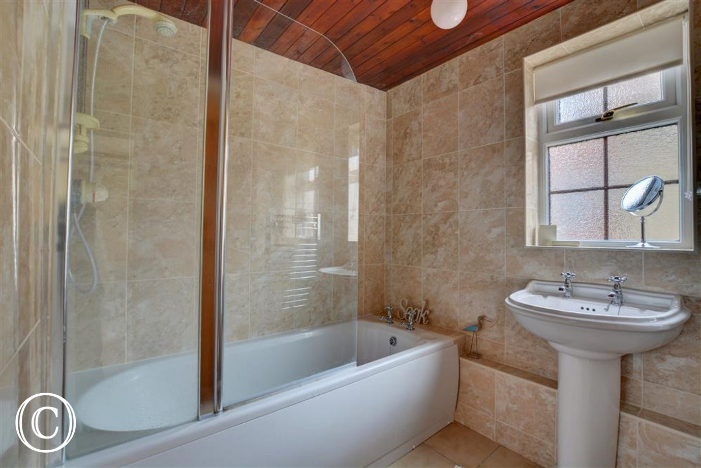 Fully tiled bathroom with bath and over bath shower