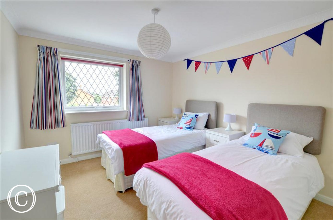 A cheerful twin bedded room with fresh white bed linen and accessories in bright colours and bunting adorning the wall.