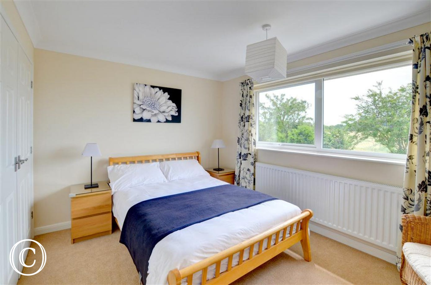 Double bedroom, nicely presented with double bed, bedside tables and large window, with floral blue and white curtains.