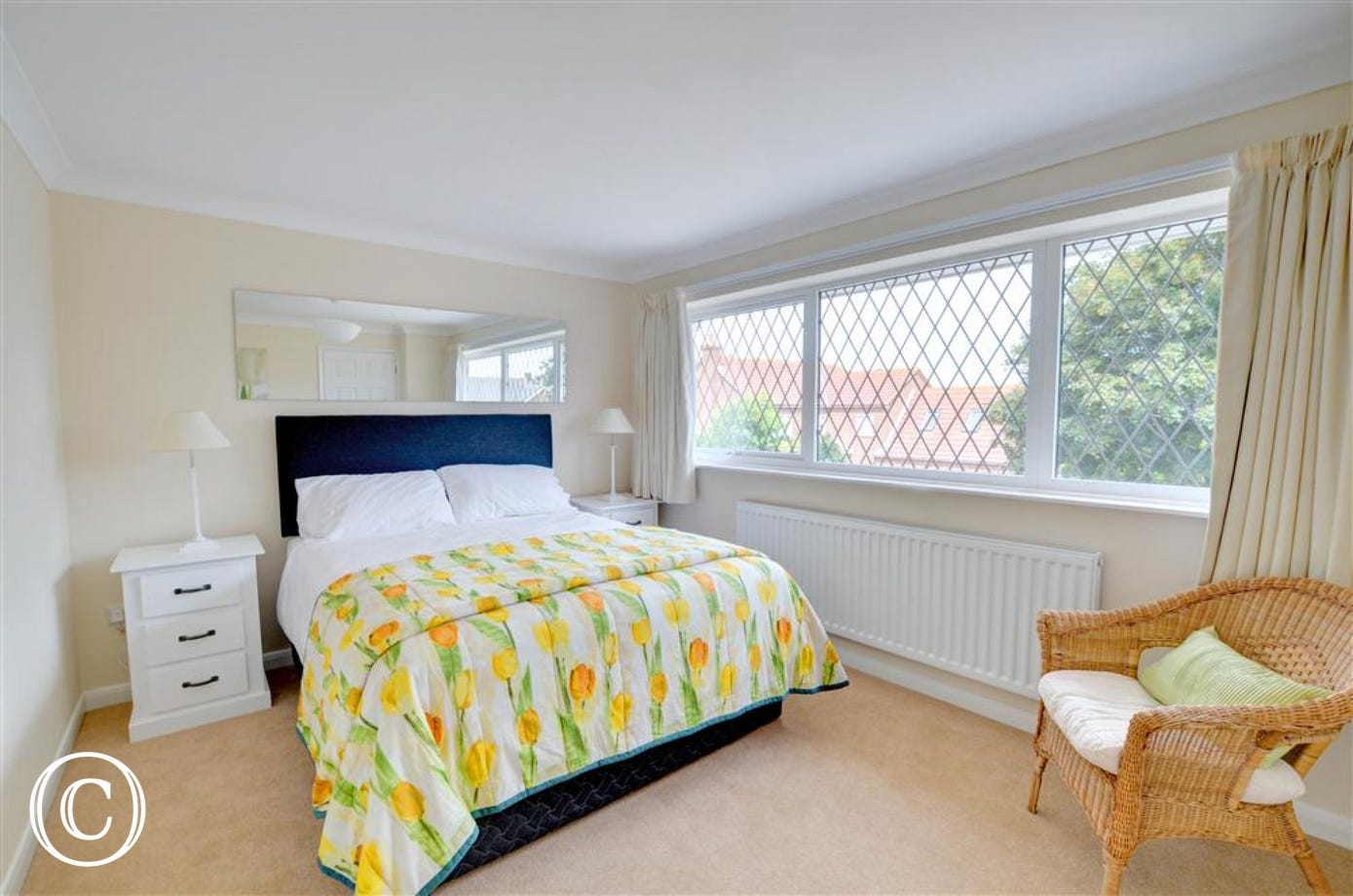 The Master bedroom is on the front of the property, again beautifully presented with white bed linen and cheery yellow floral bed cover.