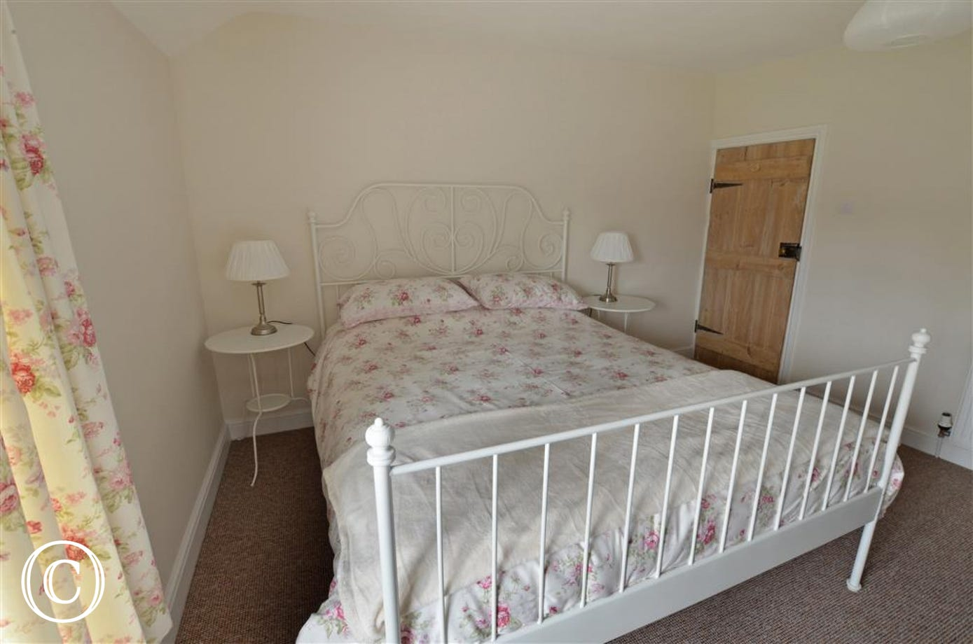 A comfortable double bed with a pretty ironwork bed frame.